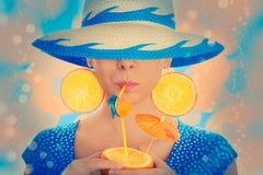 有橙味饮料和橙色戴帽子的切片耳环的女孩 库存照片