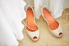 有橙红皮鞋的内底的,与一部分的顶看法美丽的妇女` s裸体泵浦鞋子的白色布料模糊在前景 免版税库存图片