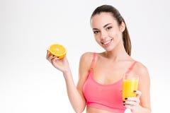 有橙色一半的健身女孩和杯汁液 免版税库存照片