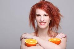 有橙色一半的微笑的红发妇女 图库摄影