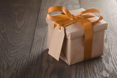 有橙色丝带弓和空标识符的土气礼物盒 库存照片