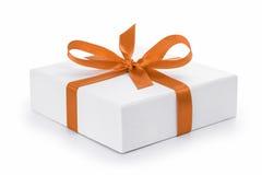 有橙色丝带弓的白色织地不很细礼物盒 图库摄影