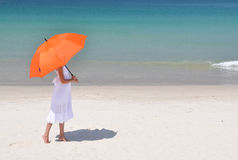 有一把伞的女孩在沙滩 免版税库存照片