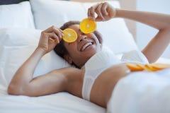 有橙色切片的少妇 年轻黑人妇女在床上 图库摄影