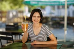 有橙色圆滑的人的愉快的女性 咖啡馆的华美的妇女在被弄脏的背景 夏天咖啡馆概念 复制空间 库存照片