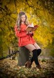 有橙色外套读书的美丽的典雅的女孩坐树桩秋季公园 有金发读书的年轻俏丽的妇女 免版税库存图片