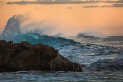 有橙色天空的Shorebreak蓝色波峰在日落背景 库存图片
