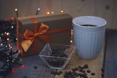 有橙色弓的一个棕色礼物盒和在tablenn的蓝色杯子 免版税库存图片
