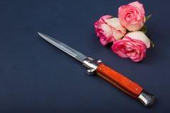有橙色把柄的折叠的刀子在与玫瑰的蓝色背景 免版税库存图片