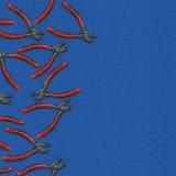 有橙色把柄的钳子在与一个地方的蓝色牛仔布背景文本的 图库摄影