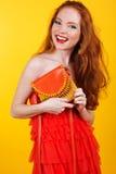 有橙色提包的红发微笑的女孩 库存照片
