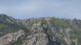 有橙色条纹的黄色滑翔伞在一个美好的山区飞行以灰色大岩石为背景 股票录像