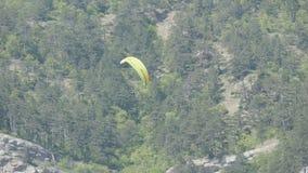 有橙色条纹的黄色滑翔伞在一个美好的山区飞行以灰色大岩石为背景 影视素材