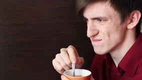 有橙色杯子的一个年轻人在他的手上搅动茶匙,看在旁边生气 影视素材