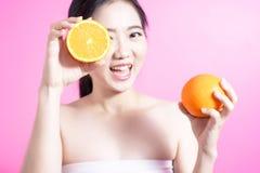 有橙色概念的亚裔妇女 微笑和拿着桔子的她 秀丽面孔和自然构成 隔绝在桃红色背景 库存图片