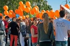 有橙色气球的学生在劳动节示范参与在伏尔加格勒 免版税库存照片