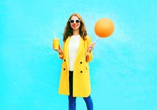 有橙色气球的时尚俏丽的微笑的妇女拿着杯子果汁 免版税库存图片