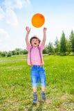 有橙色气球的逗人喜爱的男孩在绿色领域 免版税库存照片