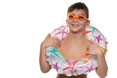 有橙色游泳的风镜的愉快的男孩和可膨胀的休息的圈子、概念和体育,在白色背景,拷贝空间 免版税库存照片