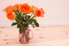 有橙色玫瑰的瓶子 免版税图库摄影