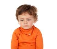 有橙色球衣的哀伤的滑稽的婴孩 免版税库存图片