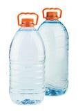 有橙色盖帽的两个大塑料水瓶 免版税库存照片