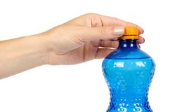 有橙色盖帽的蓝色塑料水瓶,隔绝在白色背景,用手 免版税库存图片