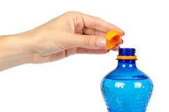 有橙色盖帽的蓝色塑料水瓶,隔绝在白色背景,用手 库存图片