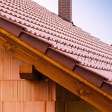 有橙色砖墙、屋顶和烟囱的新房 房屋建设工作者概念 库存图片