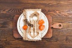 有橙色空泡和银器的碗筷 库存照片