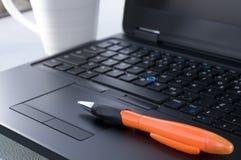 有橙色笔的膝上型计算机键盘 库存照片