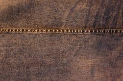 有橙色缝的布朗牛仔裤 免版税库存照片