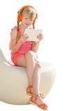 有橙色耳机和白色片剂个人计算机的坐的微笑的女孩 免版税库存照片
