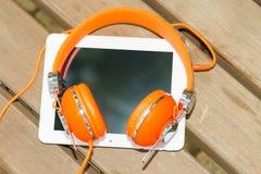 有橙色耳机的白色片剂个人计算机在木长凳 免版税库存图片