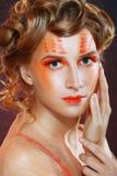 有橙色艺术性的脸的妇女 库存照片