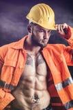 有橙色衣服的性感的建筑工人开放在赤裸躯干 库存图片