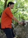 有橙色衬衣的人设法拉扯不可思议的剑Excalibur 库存图片