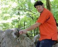 有橙色衬衣的人采取传奇剑Excalibur 免版税图库摄影