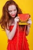 有橙色钱包的红发微笑的女孩 库存照片