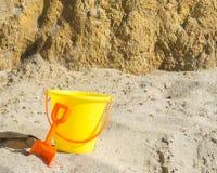 有橙色铁锹的黄沙桶在陡峭的岩石墙壁附近的海滩 图库摄影