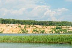 有橙色黄沙小山山的蓝色在上面的湖和森林反对天空 库存图片