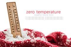 有次级零的温度的温度计在随风飘飞的雪被包裹的红色围巾非常突出  库存照片