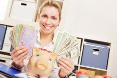 有欧元和美元金钱的妇女在办公室 库存照片