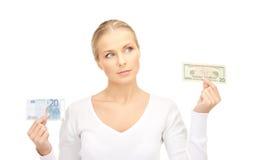 有欧元和美元金钱笔记的妇女 免版税图库摄影