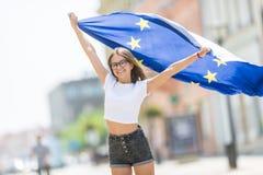 有欧盟的旗子的逗人喜爱的愉快的少女在街道的某处在欧洲 图库摄影