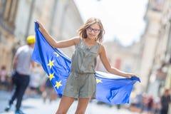 有欧盟的旗子的逗人喜爱的愉快的少女 免版税库存图片