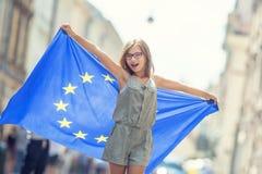 有欧盟的旗子的逗人喜爱的愉快的少女 库存图片