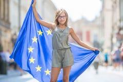有欧盟的旗子的逗人喜爱的愉快的少女 库存照片