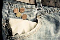 有欧洲硬币的老退色的牛仔裤在空的口袋 免版税图库摄影