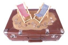 有欧洲硬币的葡萄酒手提箱在玩具海滩睡椅前面说谎 免版税库存照片